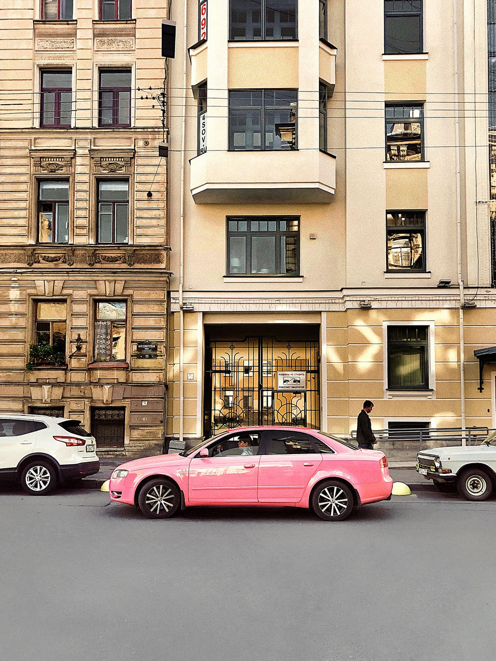 pink car in front of building